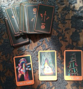 3 tarot cards on a table next to deck