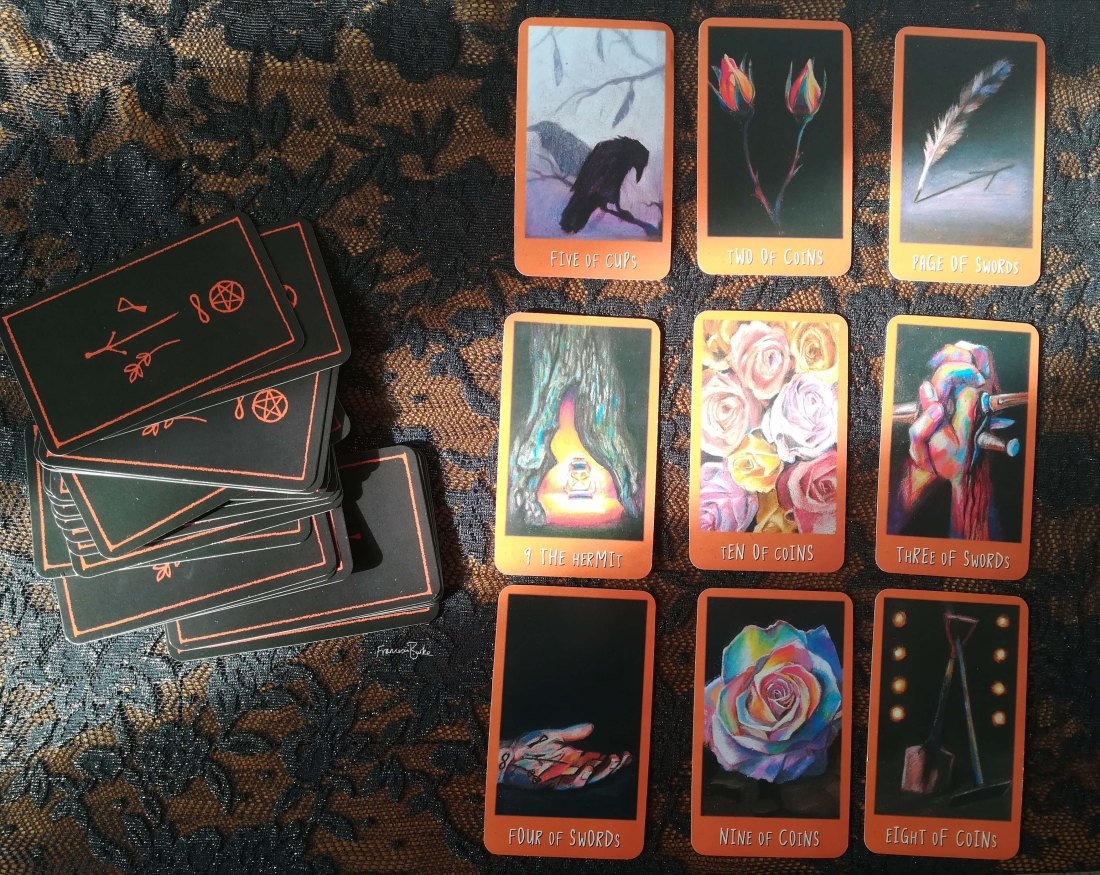 9 Raven's Prophecy tarot cards on table next to deck