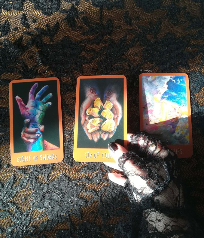 3 Raven's prophecy tarot cards held by gloved hand