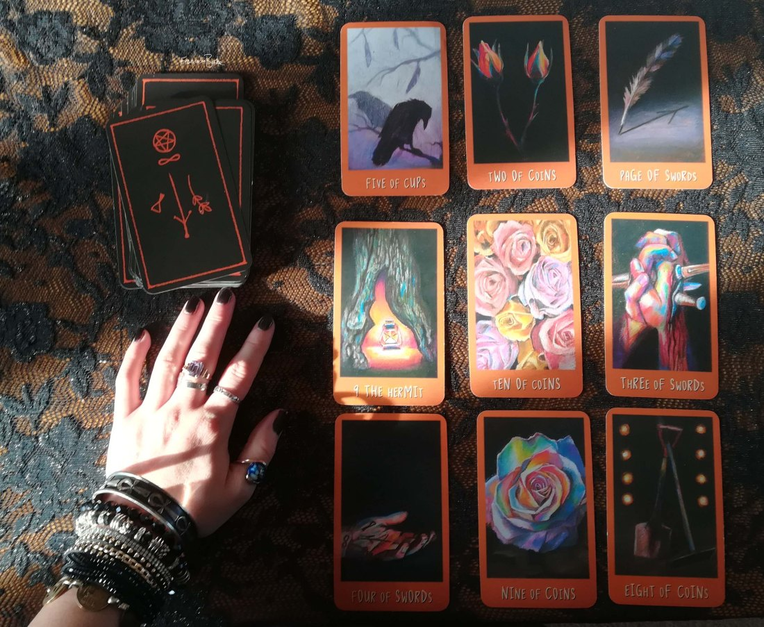 9 Raven's Prophecy tarot cards with a hand