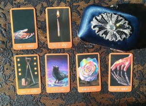 clutch bag next to 6 Raven's Prophecy tarot cards