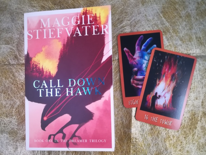 paperback of 'Call Down the Hawk' by Maggie Steifvater next to The Tower and Eight of Swords from Raven's Prophecy Tarot