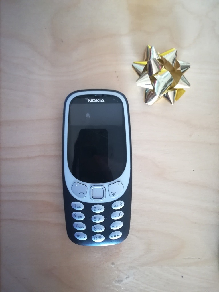 Nokia Brick phone next to a gold foil bow