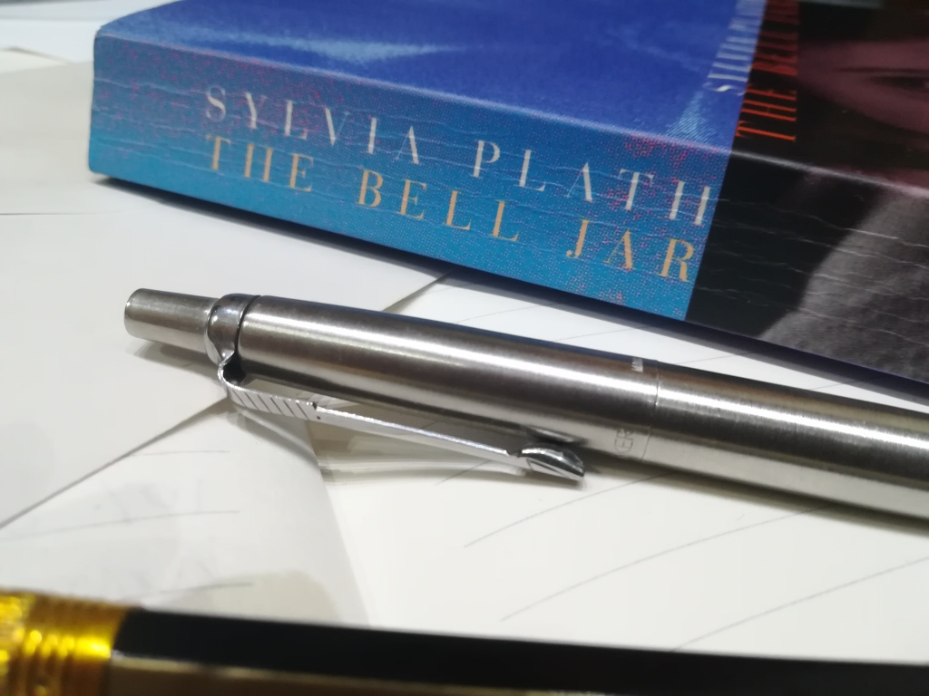 Spine of 'The Bell Jar' by Sylvia Plath, plus a pen and pencil, on lined paper and envelopes.