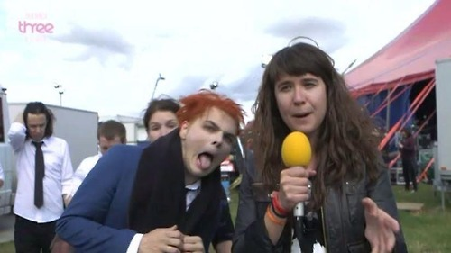 Gerard Way pulling a face next to a BBC reporter at Reading Festival in 2014