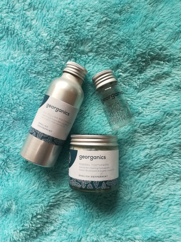Oil pulling mouthwash bottle, glass dental floss jar and solid toothpaste jar by Georganics, on a blue blanket.