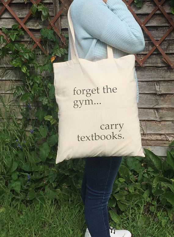 person modelling tote bag reading 'forget the gym... carry textbooks.'